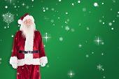 Jolly Santa smiling at camera against green