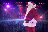 Santa Claus shows his side to camera against digitally generated nightclub under lights