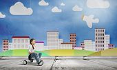 Cute girl against drawn background riding three wheeled bike