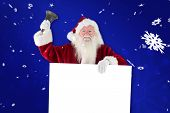 Santa holds a sign and rings his bell against blue snowflake background