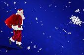 Santa claus carrying sack against blue snowflake background