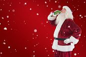 Father Christmas drinks beer with closed eyes against red background