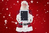 Santa presents a tablet PC against red snowflake background