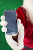 Santa claus showing smartphone against green snowflake background