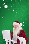 Santa pays with credit card on a laptop against green snowflake background