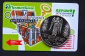 Kiev,Ukraine.Dec 22.Illustrative editorial.Ukrainian commemorative coin in memory Revolution of Dignity with card of Privat Bank as background .At December 22,2014 in Kiev, Ukraine
