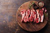 picture of cumin  - Raw fresh lamb ribs with pepper and cumin on wooden cutting board on dark background - JPG