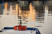 picture of life-boat  - Red life buoy on nose of old boat in sea at sunset