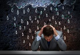 stock photo of annoying  - Depressed tired businessman with hands on head - JPG