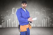 pic of clipboard  - Handyman in blue overall writing on clipboard against hand drawn city plan - JPG