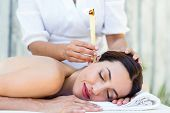 stock photo of ear candle  - Relaxed brunette getting an ear candling treatment at the spa - JPG