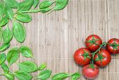 stock photo of bamboo leaves  - green spinach leaves and branch of ripe tomatoes on a bamboo mat - JPG