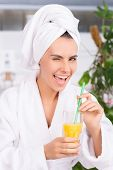 stock photo of eye-wink  - Beautiful young woman in bathrobe holding s glass with juice and winking to you