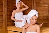 stock photo of sauna woman  - Two attractive women wrapped in towel relaxing in sauna and keeping eyes closed