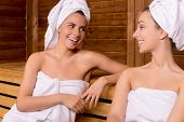 foto of sauna woman  - Two attractive women wrapped in towel talking to each other and smiling while relaxing in sauna