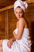 stock photo of sauna woman  - Beautiful young woman wrapped in towel relaxing in sauna and keeping eyes closed - JPG