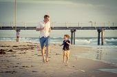 stock photo of barefoot  - young happy father playing on the beach with little son running excited with barefoot in sand and water the kid smiling and having fun together with dad in Summer vacation concept - JPG