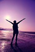 image of open arms  - cheering young woman hiker open arms on sunrise beach - JPG