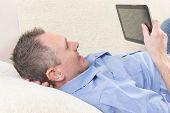picture of deaf  - Smiling Deaf man talking using tablet at home - JPG
