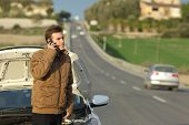 picture of breakdown  - Happy man calling roadside assistance for his breakdown car in a country road - JPG