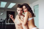 picture of bdsm  - Sexy macho man holding handcuffs with milf lover bdsm - JPG