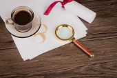 picture of private detective  - Coffee cup paper sheets and detective hat on old Wooden table - JPG