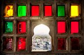 picture of rajasthani  - Town view from the colorful mosaic window in City Palace museum of Udaipur Rajasthan India - JPG