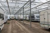 stock photo of campervan  - Caravan parking in an empty Dutch Greenhouse - JPG