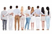 foto of bonding  - Full length rear view of group of diverse people bonding to each other and standing against white background while one African man looking over shoulder and smiling - JPG