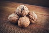 picture of walnut  - Walnut kernels and whole walnuts on rustic old wooden table