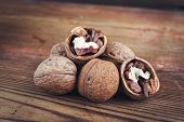 stock photo of walnut  - Walnut kernels and whole walnuts on rustic old wooden table glass jar