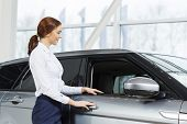 foto of showrooms  - Young pretty woman dealer in showroom standing near car  - JPG