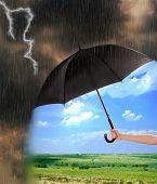 pic of rain cloud  - Black umbrella in hand protecting good weather from dark clouds of rain - JPG