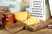 stock photo of grating  - Grated cheese on wooden cutting board on blurred background - JPG