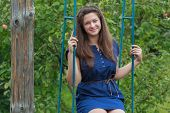 stock photo of swing  - Portrait of brunette girl in navy blue sundress is sitting on handmade swing - JPG