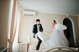 pic of pillow-fight  - Young Beautiful Wedding Couple At The Hotel Room Fight Pillow  - JPG
