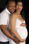 Sexy beautiful pregnant Indian woman and african male embracing