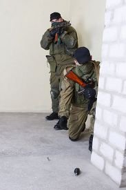 image of ak-47  - insurgents with AK 47 throws a grenade inside the building - JPG