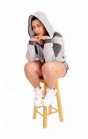 pic of hoodie  - A lovely young woman in a gray hoodie and shorts sitting on a chair