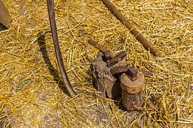 pic of scythe  - Hammer and iron tool for sharpening scythe on the tree stump - JPG