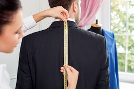 pic of measurement  - Beautiful female tailor is standing near her male client - JPG