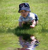 Baby In The Grass By Water