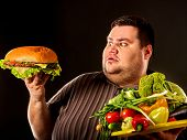 Diet fat man who makes choice between healthy and unhealthy food. Overweight male with hamburgers. C poster