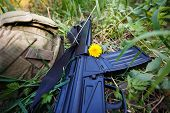 Military Helmet, Rifle And A Flower In The Grass Close Up poster