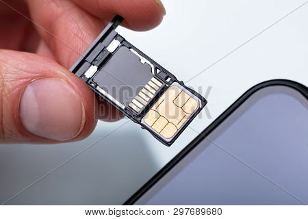 poster of Person Inserting Sim Card In Cellphone