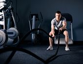 Muscular Man is Doing Battle Rope Exercise while Working out in Dark Modern Training Fitness Gym. Cr poster