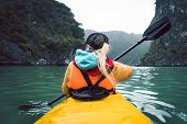Girl Kayaking On The Seaside Of Halong Bay In Vietnam. Woman Rowing Oars In The Boat. The View From  poster