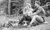 Couple Romantic Date Near Bonfire In Forest. Couple Relaxing Sit On Log Having Snacks. Pleasant Picn poster