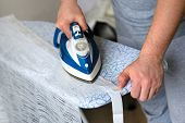 Man Irons Clothes On Ironing Board With Blue Iron. Housework And Household Concept. Clothing Ironing poster