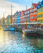 Nyhavn View With Boats By Embankmentat Sunset, People Walking And Sitting At Restaurants, Copenhagen poster
